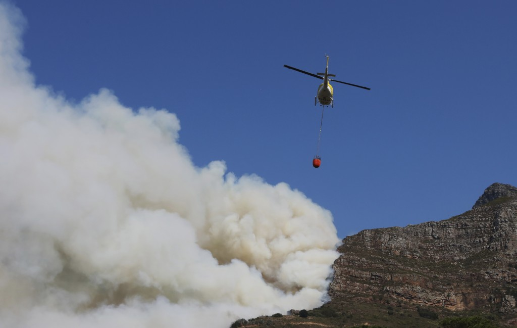 A helicopter drops water over a fire at Rhodes Memorial on Table Mountain, Cape Town, South Africa, Sunday, April 18, 2021. A wildfire raging on the s...