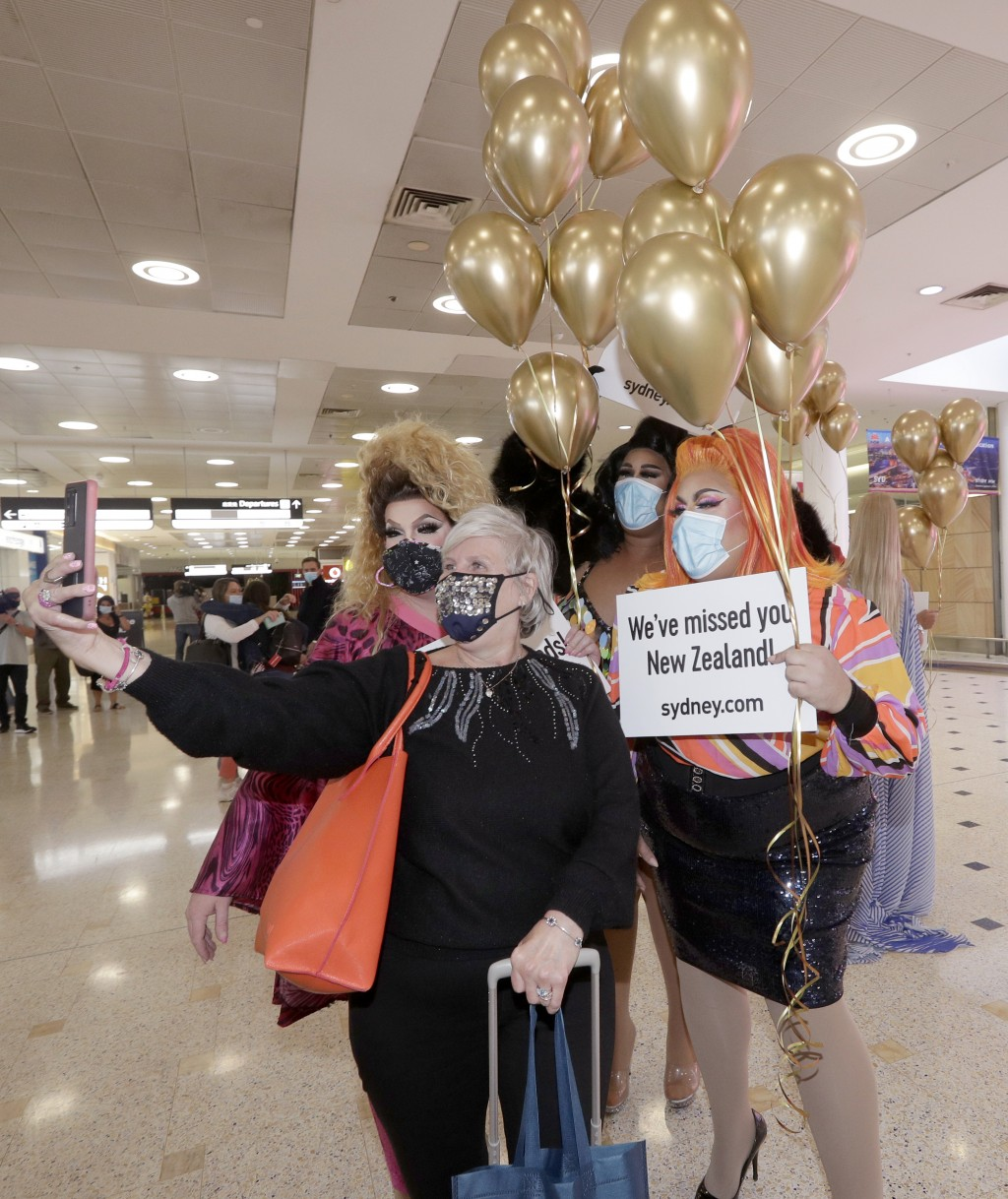 A passenger from New Zealand, second left, poses with drag queens as they welcome her at Sydney Airport in Sydney, Australia, Monday, April 19, 2021, ...