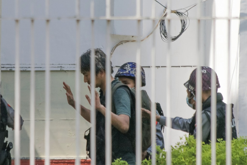 In this Feb. 26, 2021, photo, Japanese journalist Yuki Kitazumi raises his hands as he is escorted by police upon arrival at the Myaynigone police sta...