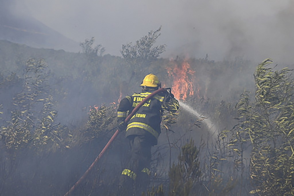 A fire rages on the slopes of Table Mountain, in Cape Town South Africa, Monday, April 19, 2021. Residents were evacuated from Cape Town neighborhoods...