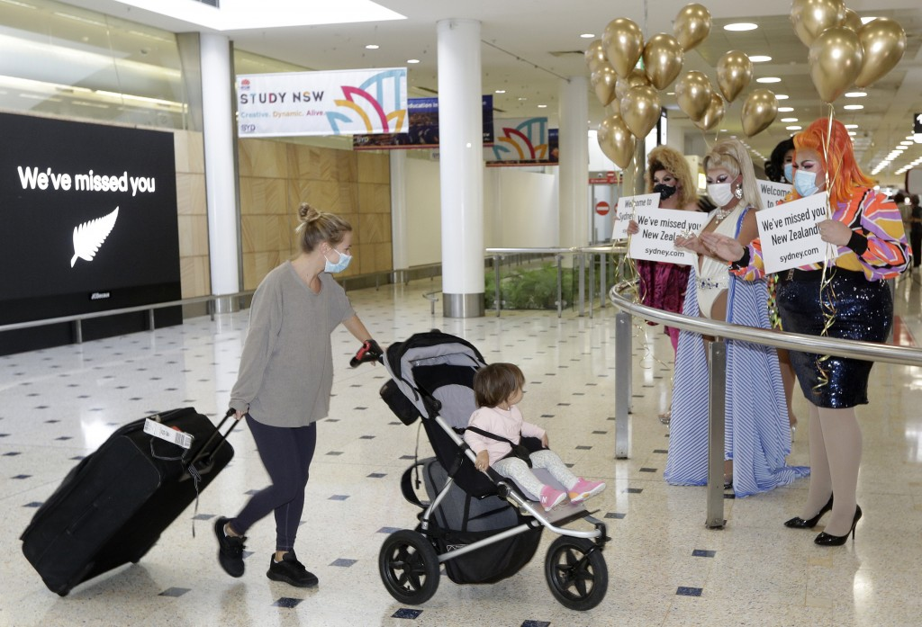 Passengers from New Zealand are welcomed by drag queens as they arrive at Sydney Airport in Sydney, Australia, Monday, April 19, 2021, as the much-ant...