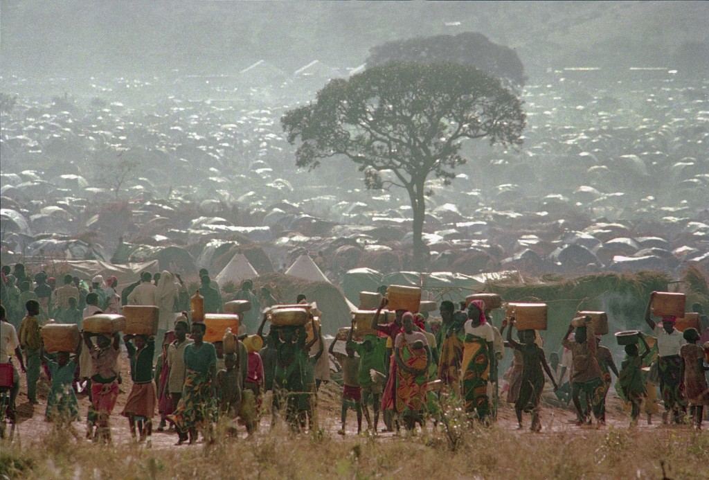 FILE - In this Tuesday, May 17, 1994 file photo, refugees who fled the ethnic bloodbath in neighboring Rwanda carry water containers back to their hut...