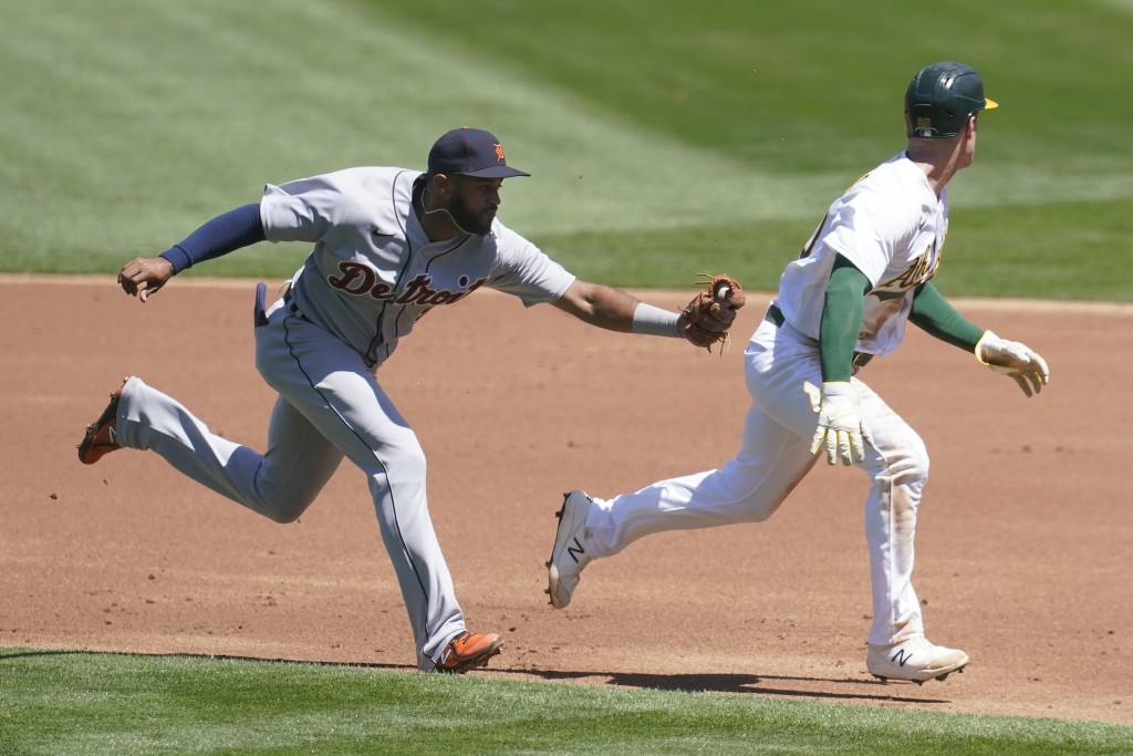 Oakland Athletics Mark Canha, right, is caught in a rundown before being tagged out by Detroit Tigers shortstop Willi Castro, left, during the first i...