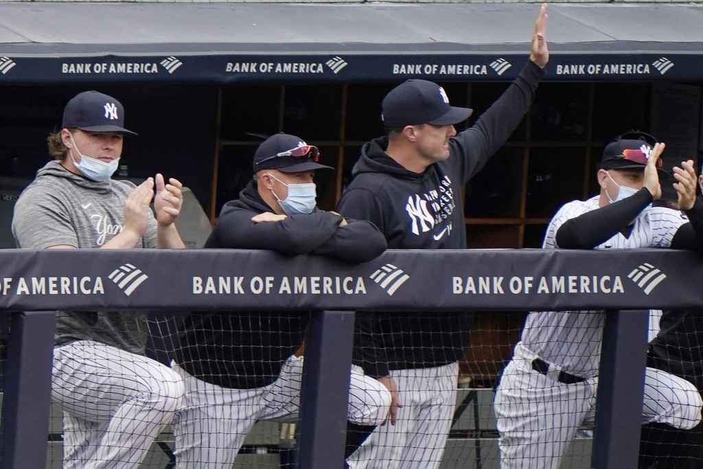 New York Yankees outfielder Jay Bruce, third from left, waves from the dugout as injured first baseman Luke Voit, left, applauds, while outfielder Bre...
