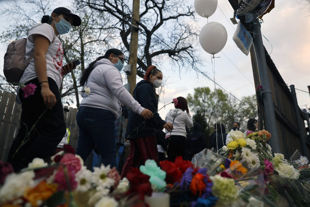 People pay tribute as they attend a peace walk honoring the life of police shooting victim 13-year-old Adam Toledo, Sunday, April 18, 2021, in Chicago...