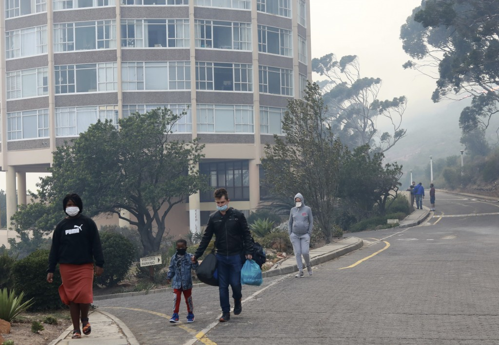 Residents leave their a residential building due to a fire on the slopes of Table Mountain, in Cape Town South Africa, Monday, April 19, 2021. Residen...