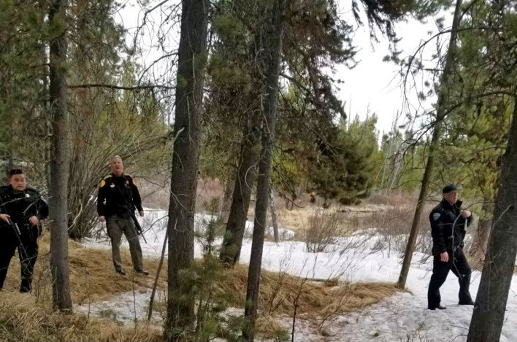In this photo provided by the Gallatin County Sheriff's Office, officers from the sheriff's office and West Yellowstone Police Department are seen nea...