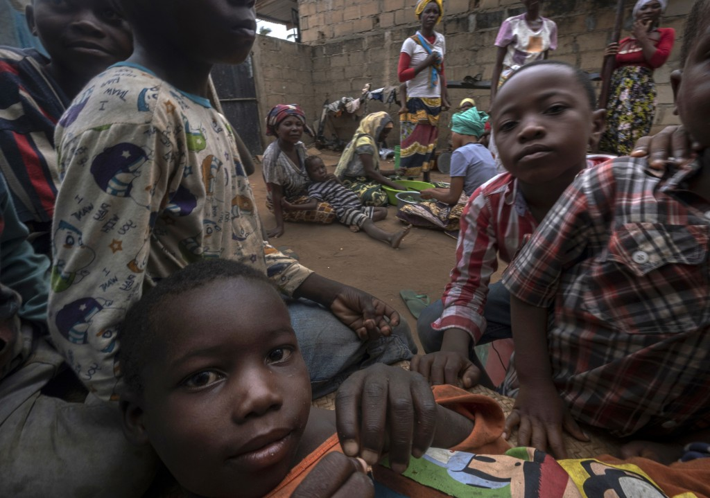 Displaced women with their children wait for assistance at a building used by refugees as shelter in Pemba, Mozambique, after they fled attacks in Pal...