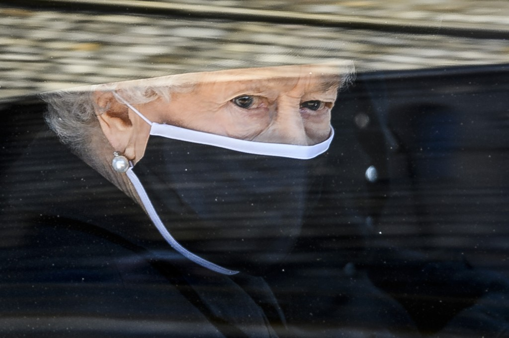 FILE - In this Saturday April 17, 2021 file photo, Britain's Queen Elizabeth II follows the coffin in a car as it makes it's way past the Round Tower ...