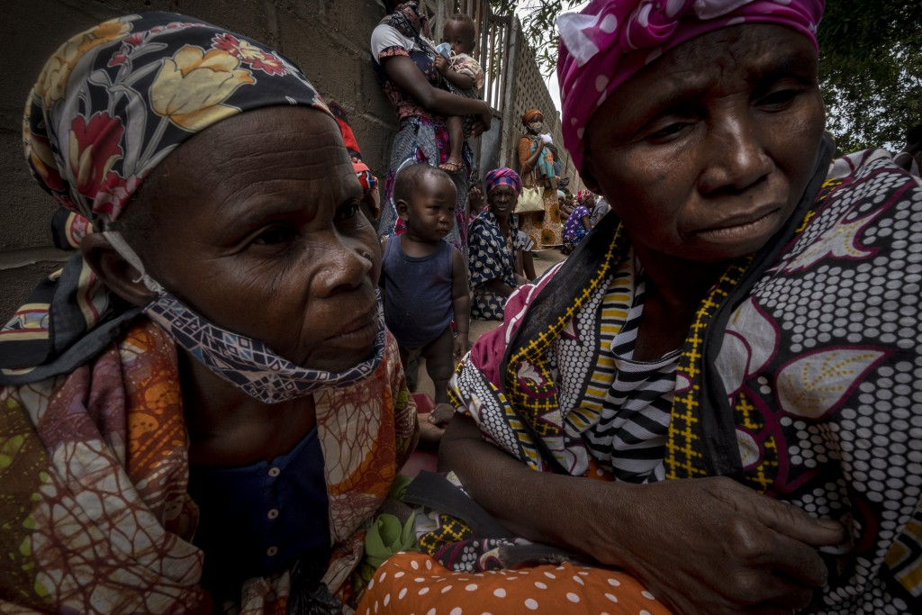 Displaced women and children wait for assistance at a building used by refugees as shelter in Pemba, Mozambique, after they fled attacks in Palma in N...
