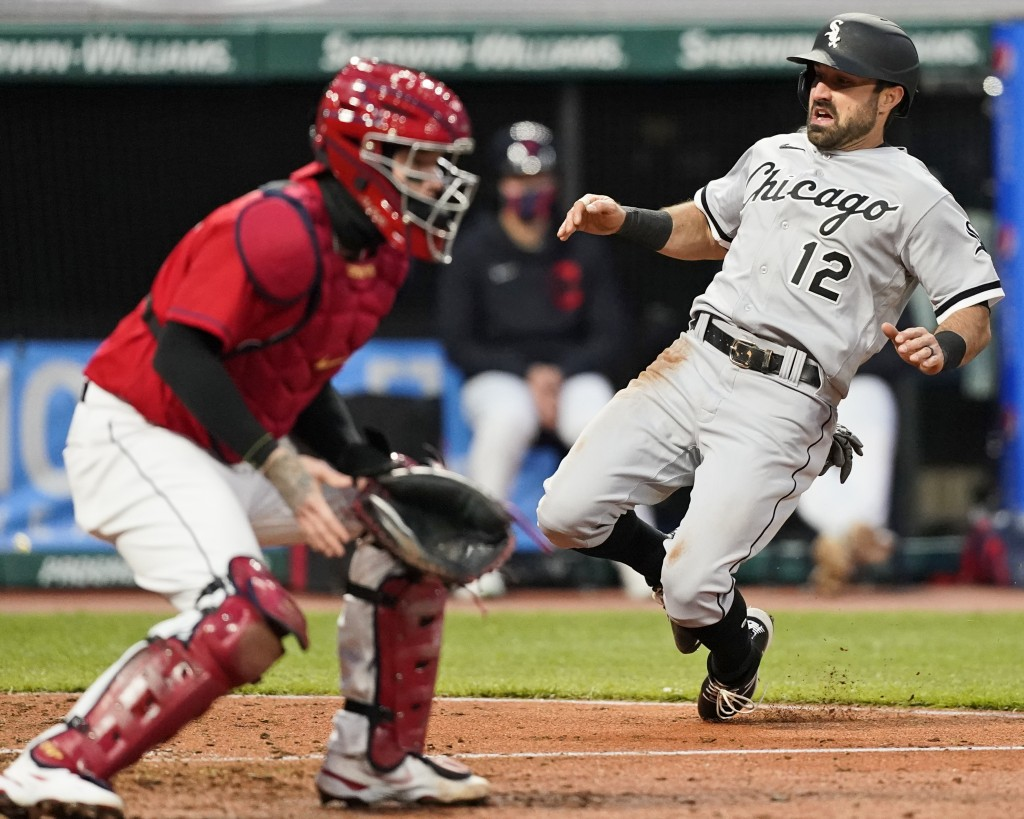 Chicago White Sox's Adam Eaton, right, scores as Cleveland Indians' Roberto Perez, left, waits for the ball in the sixth inning in a baseball game, Tu...