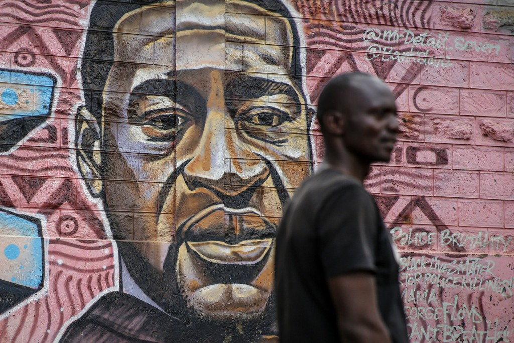 """A local resident stands next to a mural painted in June 2020 showing George Floyd with the Swahili word """"Haki"""" or """"Justice"""" in the Kibera low-income n..."""