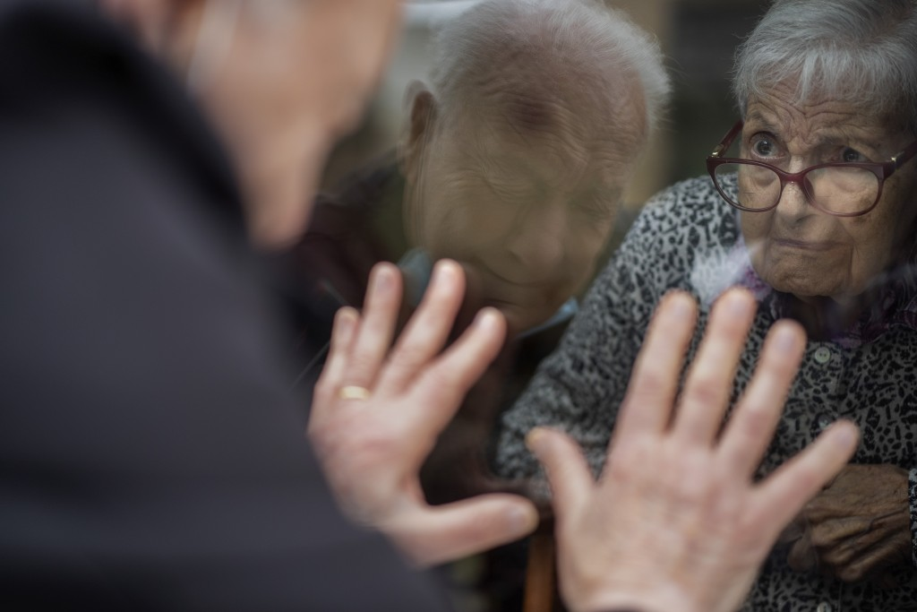 Javier Anto, 90, reacts in front of his wife Carmen Panzano, 92, through the window separating the nursing home from the street in Barcelona, Spain, W...