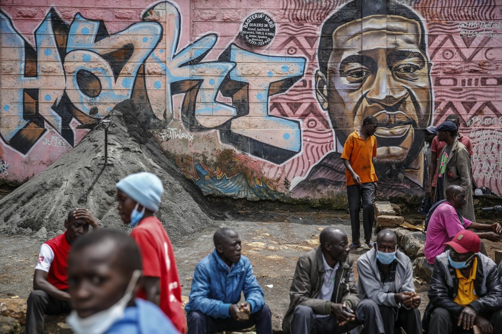 """Local residents sit next to a mural painted in June 2020 showing George Floyd with the Swahili word """"Haki"""" or """"Justice"""" in the Kibera low-income neigh..."""