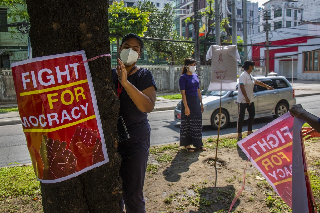 Anti-coup protesters place posters of slogans on trees along a road during a demonstration at Yangon, Myanmar on Wednesday, April 21, 2021. Aid worker...