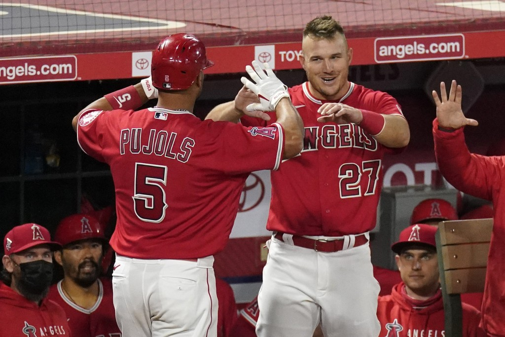 Los Angeles Angels' Albert Pujols, left, is congratulate by Mike Trout after hitting a solo home run during the seventh inning of a baseball game agai...