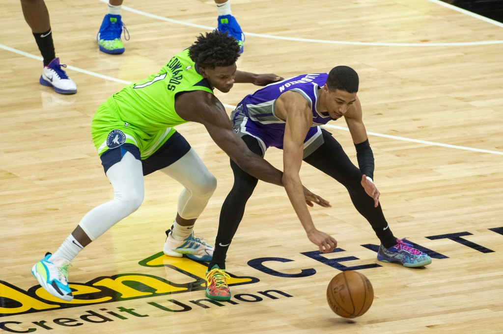 Minnesota Timberwolves forward Anthony Edwards (1) and Sacramento Kings guard Tyrese Haliburton (0) scramble for the ball during the first quarter of ...