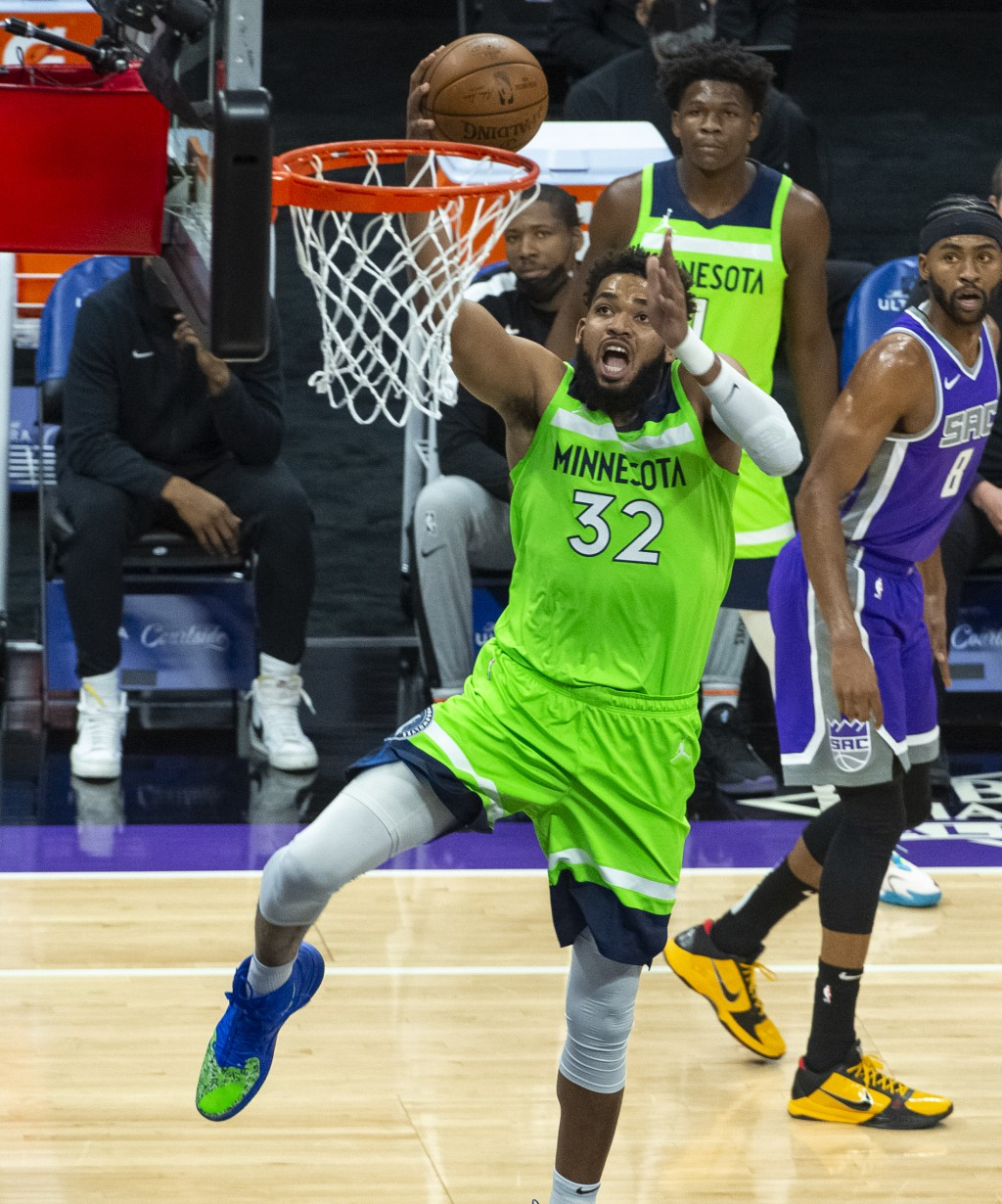 Minnesota Timberwolves center Karl-Anthony Towns (32) scores against the Sacramento Kings during the first quarter of an NBA basketball game in Sacram...