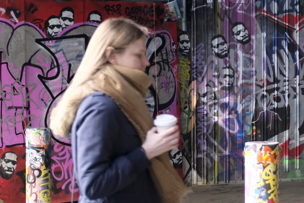 A woman walks past a mural depicting the image of George Floyd under railway arches at Waterloo Station, in London, Wednesday, April 21, 2021. After t...