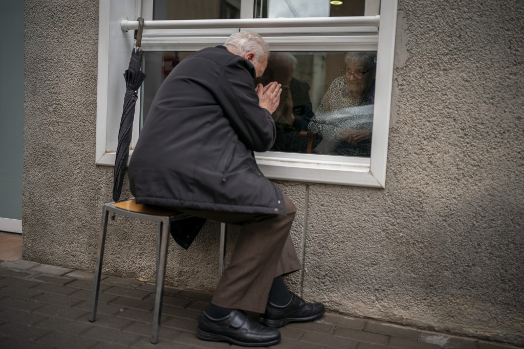 Javier Anto, 90, prays in front of his wife Carmen Panzano, 92, through the window separating the nursing home from the street in Barcelona, Spain, We...