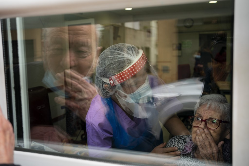 Javier Anto, 90, and his wife Carmen Panzano, 92, blow one another kisses through the window separating the nursing home from the street in Barcelona,...