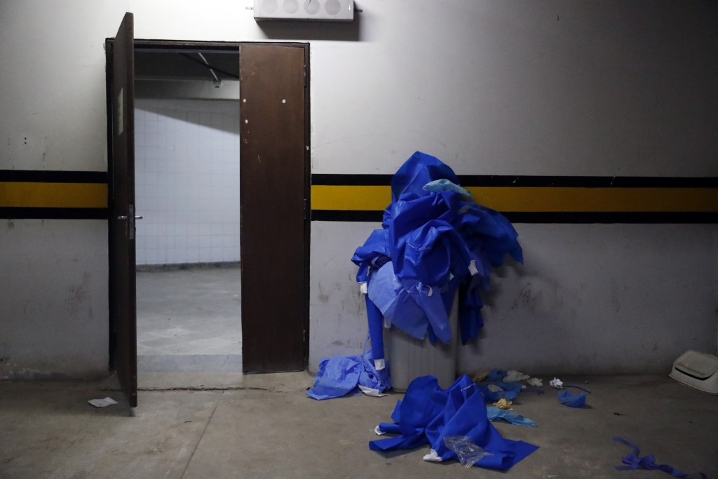 Used security gear worn in the COVID-19 area overflows a trash can at Clinicas Hospital in San Lorenzo, Paraguay, Tuesday, April 20, 2021. (AP Photo/J...