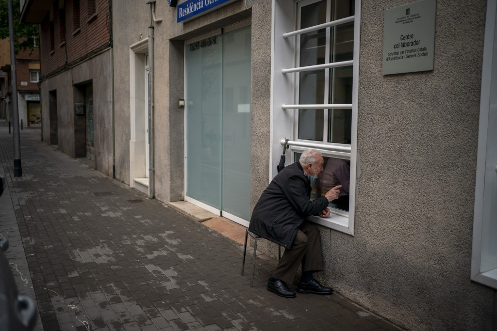 Javier Anto, 90, speaks to his wife Carmen Panzano, 92, through the window separating the nursing home from the street in Barcelona, Spain, Wednesday,...