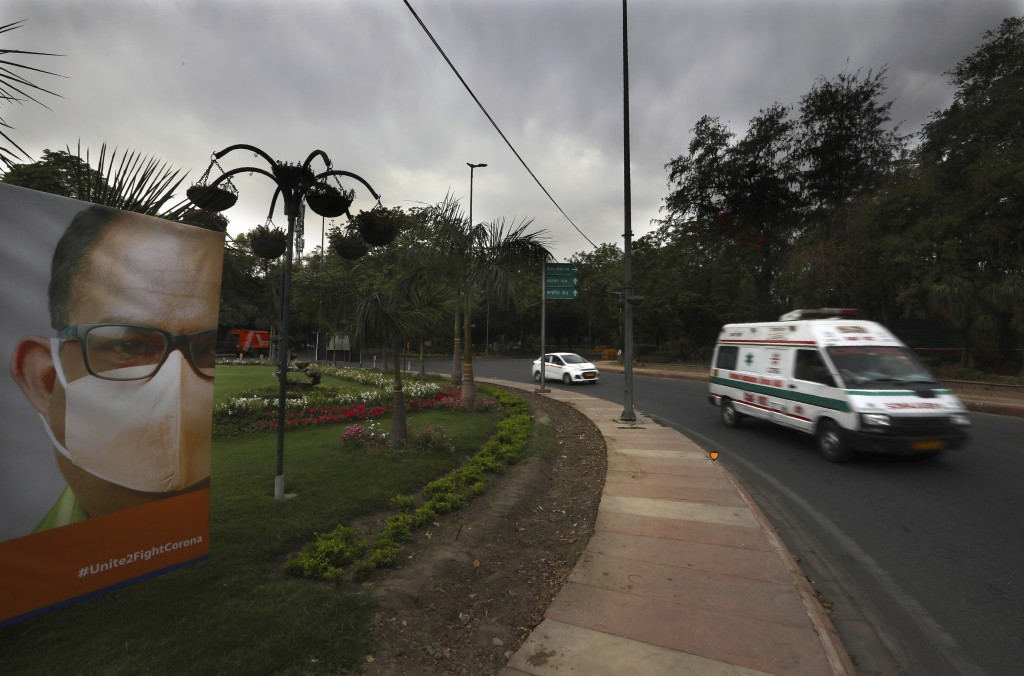 An ambulance carrying a patient drives past a Coronavirus awareness poster on a deserted street on the first day of a six-day lockdown put into place ...