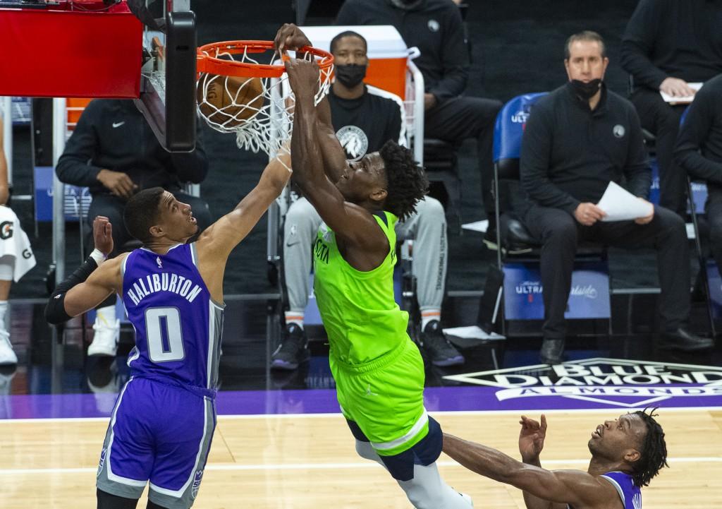 Minnesota Timberwolves forward Anthony Edwards (1) dunks as Sacramento Kings guard Tyrese Haliburton (0) defends during the first quarter of an NBA ba...