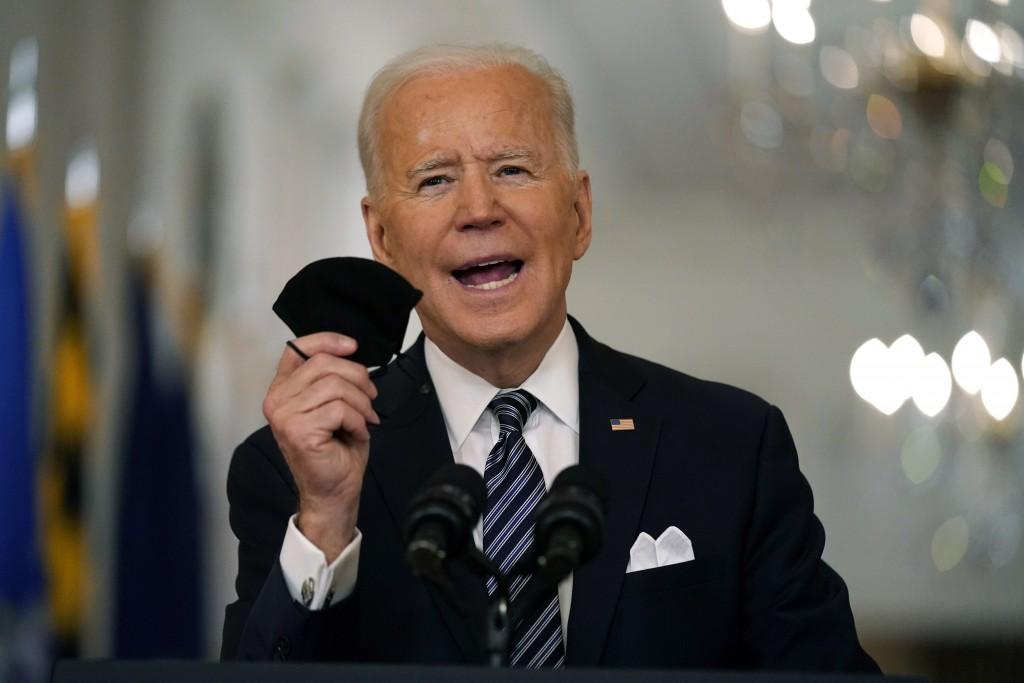 美國總統拜登日前在一場演說中手持口罩,報告美國新冠肺炎疫苗施打進度。(美聯社圖片)