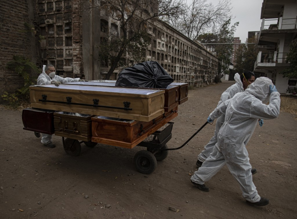 Funeral workers remove empty coffins that held remains that were later cremated at La Recoleta cemetery in Santiago, Chile, Tuesday, April 20, 2021, d...