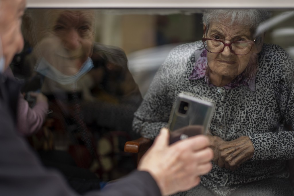 Javier Anto, 90, shows photos of their grandchildren to his wife Carmen Panzano, 92, to combat the ravages of Alzheimer's through the window separatin...