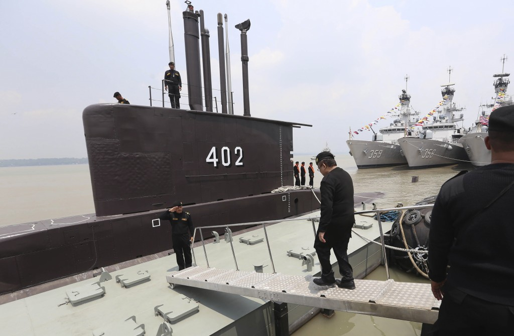 The crew of the Indonesian Navy submarine KRI Nanggala salute as an officer walks aboard at the base of the Eastern Fleet Command in Surabaya, East Ja...