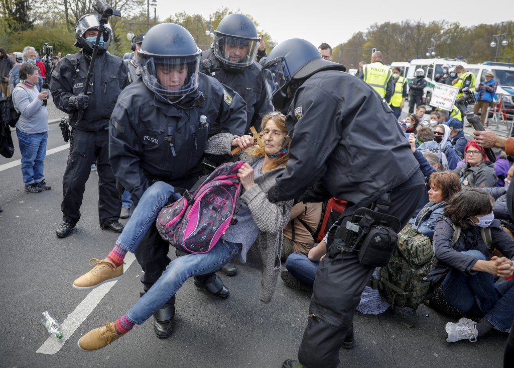 Police officers carry away a demonstrator after police stop a protest rally against the German government's policy to battle the corona virus pandemic...