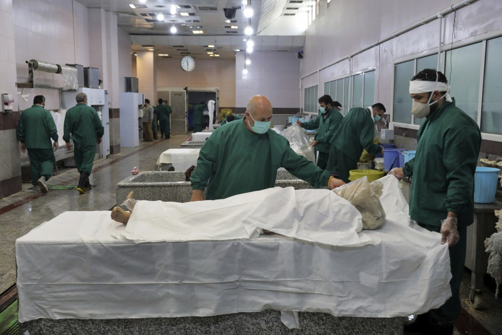 Cemetery workers prepare the bodies of people who died from COVID-19 for burial, at the Behesht-e-Zahra cemetery just outside Tehran, Iran, Wednesday,...