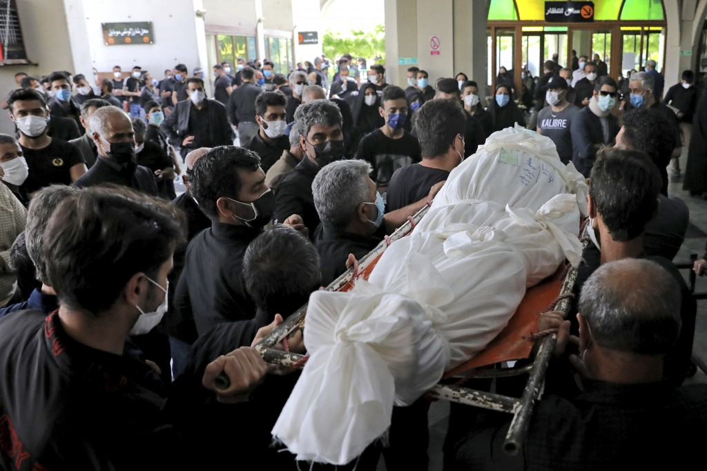 Mourners carry the body of a person who died from COVID-19, at the Behesht-e-Zahra cemetery just outside Tehran, Iran, Wednesday, April 21, 2021. Afte...