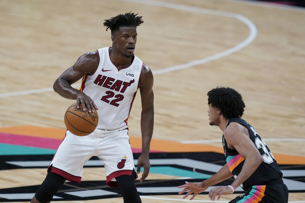 Miami Heat forward Jimmy Butler (22) drives around San Antonio Spurs guard Tre Jones (33) during the second half of an NBA basketball game in San Anto...
