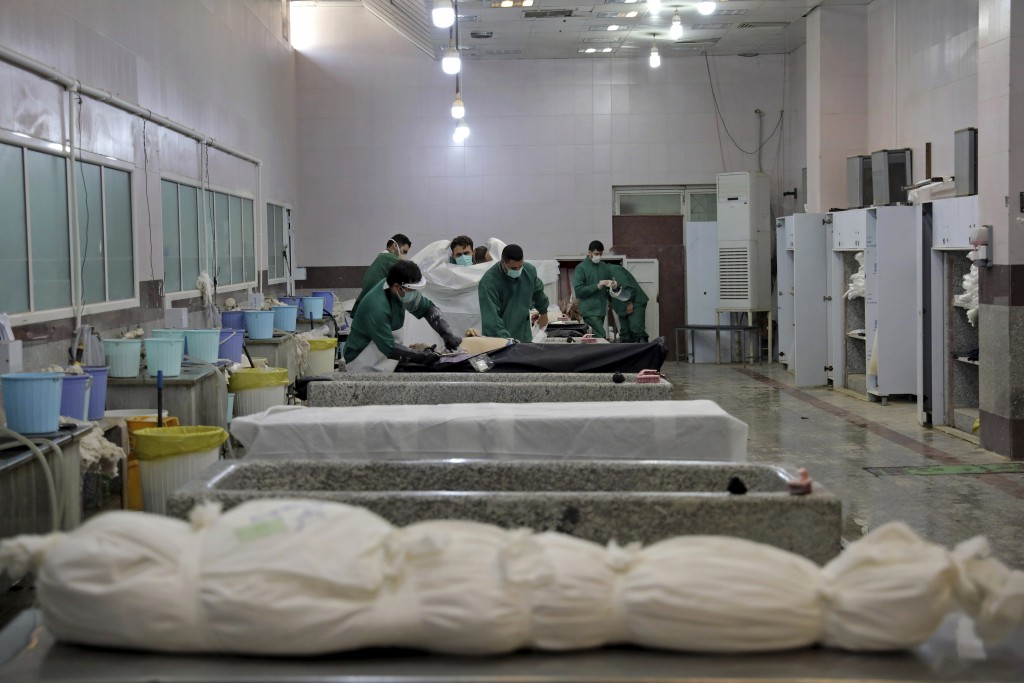 Cemetery workers prepare the body of a person who died from COVID-19 for burial, at the Behesht-e-Zahra cemetery just outside Tehran, Iran, Wednesday,...