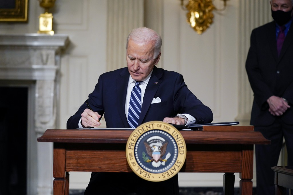 FILE - In this Jan. 27, 2021 file photo, President Joe Biden signs an executive order on climate change, in the State Dining Room of the White House i...