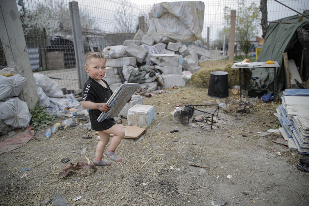 A small boy carries discarded ceramic tiles for his family's home during a raid of the National Environmental Guard through scrape littered back yards...