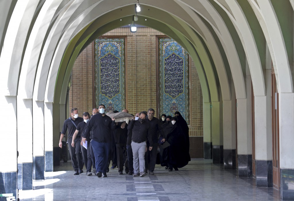 Mourners carry the body of a person who died from COVID-19 for burial, at the Behesht-e-Zahra cemetery just outside Tehran, Iran, Wednesday, April 21,...