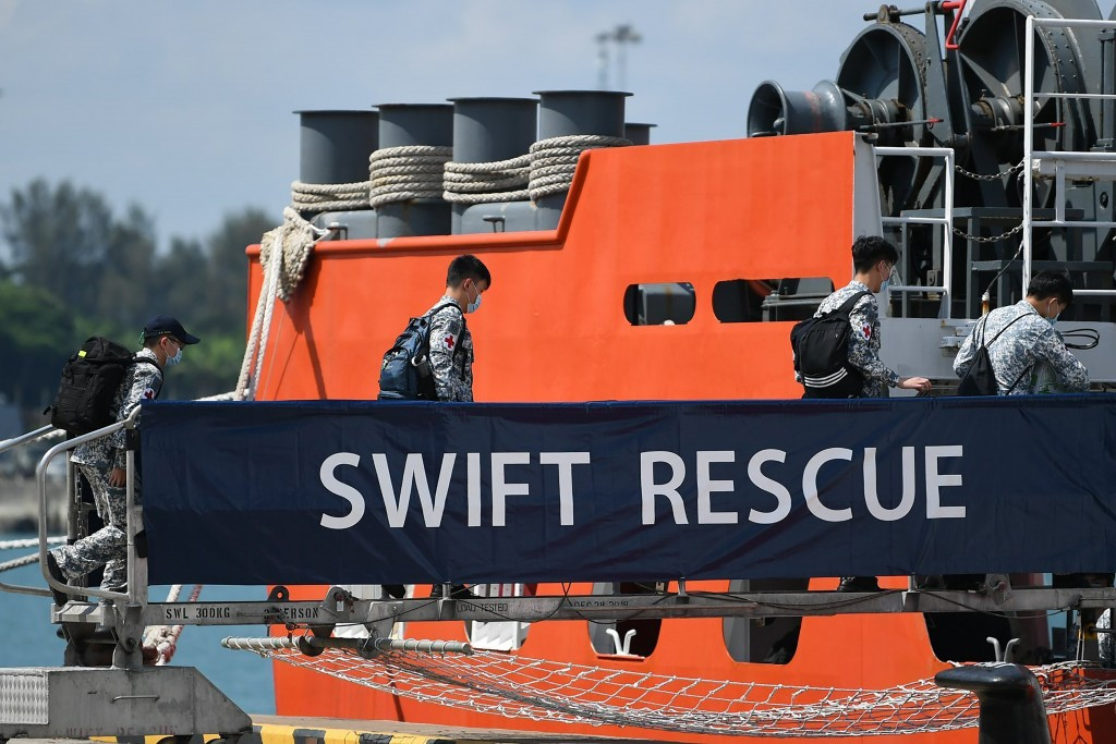 In this Apr. 21, 2021, photo, crew board the MV Swift Rescue, a submarine support and rescue vessel, before being dispatched for Indonesia from Singap...