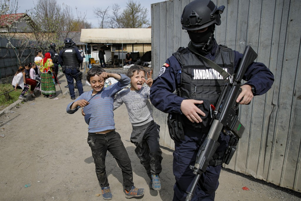 Children play next to an armed riot police officer during a raid of the National Environmental Guard through scrape littered back yards in Vidra, Roma...