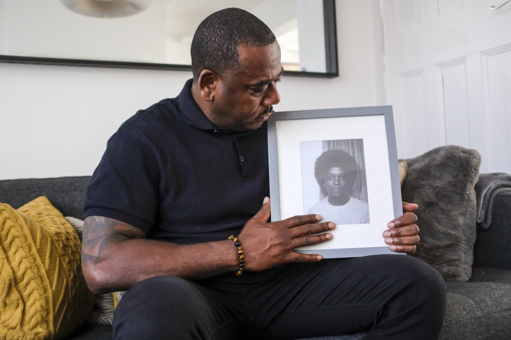 Lee Lawrence poses with a picture of his mother, Cherry Groce, in London, Wednesday, April 21, 2021. Lawrence's mother, Cherry Groce, was shot by poli...