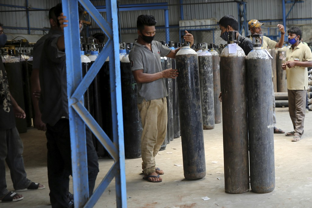 A worker arranges oxygen cylinders before loading them into a truck for supplying to different hospitals at a gas supplier facility in Bengaluru, Indi...