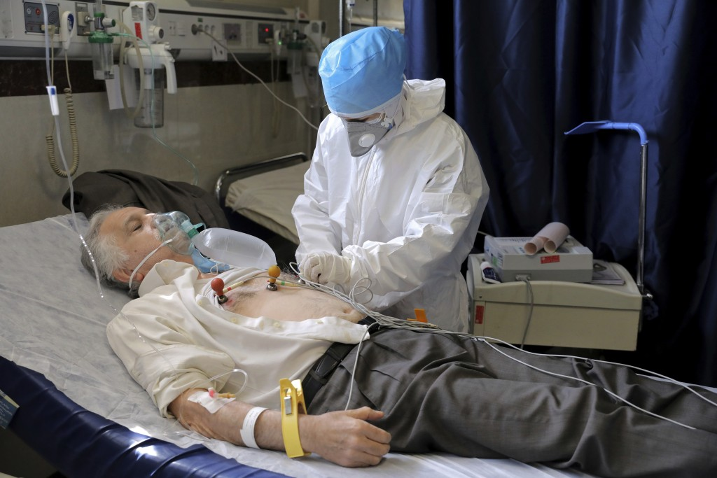 A nurse tends to COVID-19 patient at the Shohadaye Tajrish Hospital in Tehran, Iran, Sunday, April 18, 2021. After facing criticism for downplaying th...