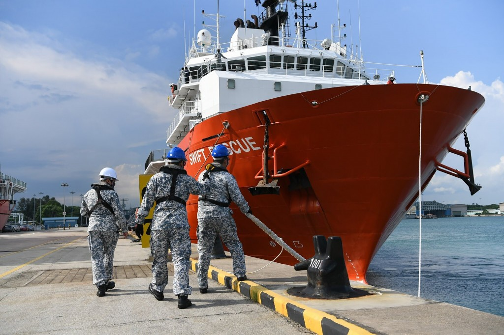 In this Apr. 21, 2021, photo, personnel from the Republic of Singapore Navy cast off lines of the MV Swift Rescue, a submarine support and rescue vess...