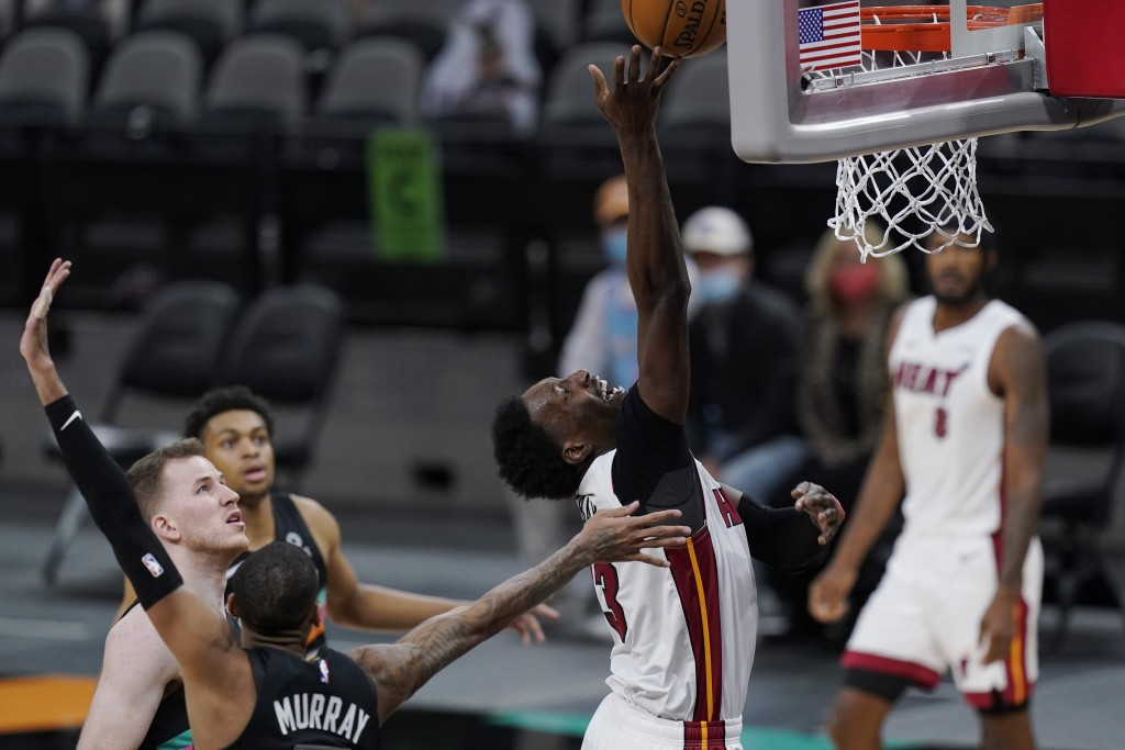 Miami Heat center Bam Adebayo (13) drives to the basket past San Antonio Spurs guard Dejounte Murray during the second half of an NBA basketball game ...