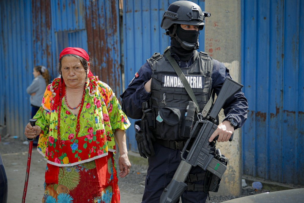 An armed riot police officer stands on a dirt road as an elderly Romanian Roma woman walks by during a raid by the National Environmental Guard on peo...