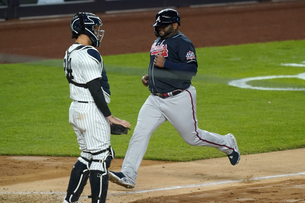 Atlanta Braves' Pablo Sandoval scores on Ehire Adrianza's fifth-inning sacrifice fly, next to New York Yankees catcher Gary Sanchez in a baseball game...